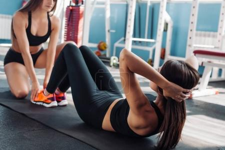 Teen girl working out in the gym coach trains