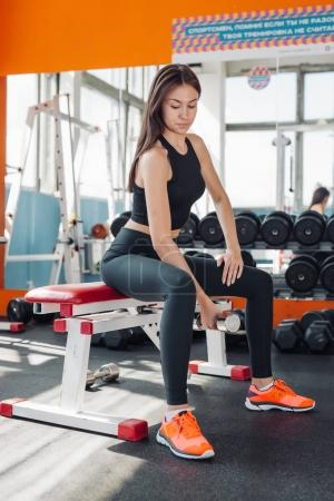 Fit woman 20s doing shoulder raises with dumbbells in gym