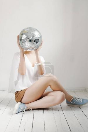 Young hipster woman holding disco ball and posing cheerfully on white background