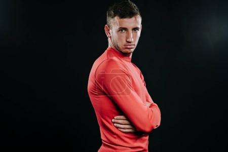 Photo for Profile view of attractive athlete man in red sportswear standing over dark background, thinking over problems in his life, holding hands, looking front. Lifestyle, sport, motivation. - Royalty Free Image