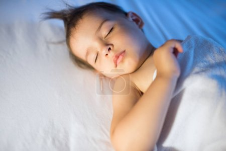 Photo for Portrait of adorable baby girl sleeping in white bed at night. Little toddler taking a nap in dark room in lamplight. Bed time for kids. Bedroom and nursery interior. - Royalty Free Image