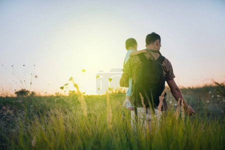 Photo for Handsome young father on his hands with his cute toddler daughter outdoor. Dad playing with his child at nature. Happy family spending time together outside at meadow and on sunset. - Royalty Free Image