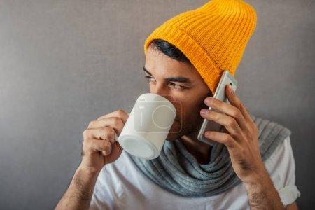 Photo pour Portrait d'un homme d'affaires jeune beau assis sur fond gris avec une tasse de café, thé, eau. S'exprimant avec un gadget, téléphone. Chapeau orange et écharpe grise. - image libre de droit