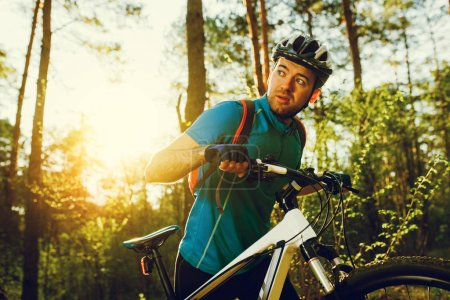 Handsome serious male biker wearing blue sports clothing, helmet and gloves, having confident and self-determined look on forest sunset or sunrise. Travel, sport, extreme concept.