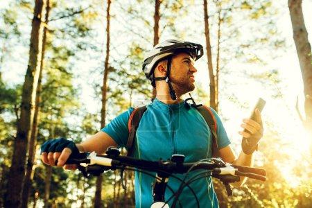 Photo pour Vue du bas prise de vue extérieure du cycliste à vélo à l'aide du navigateur sur téléphone intelligent, explorer la carte et rechercher les coordonnées GPS tout en faisant du vélo dans les montagnes. Voyages, sports, mode de vie actif et technologie moderne . - image libre de droit
