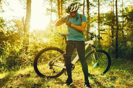 Photo pour Rare photo d'un cycliste portant des vêtements de cyclisme noir et casque de protection usure au cours de la séance d'entraînement en bois. Personnes, mode de vie sain actif et extrême. - image libre de droit