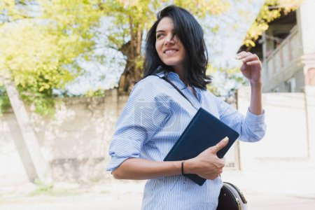 Cheerful brunette business female manager using notebook to planning the time for new projects in outdoor. Young smart student wearing blue shirt on the street. Business, people, lifestyle concept.