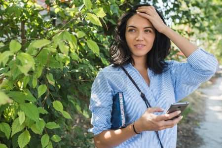 Photo for Stylish Caucasian woman using online communication with free wireless internet connectionon her web-enabled smart phone to navigate gps. Lifestyle, business and people concept. - Royalty Free Image