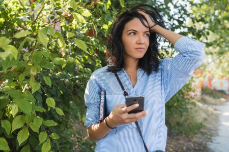 Photo for Worried stylish Caucasian student girl waiting her colleagues on the street using  online communication with free wireless internet on her web-enabled smart phone. Lifestyle and people concept. - Royalty Free Image