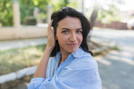 Photo pour Tir en plein air de charmante jeune femme, portant une chemise bleue, arranger ses cheveux regarder agréablement dans la caméra. Jeune jolie fille avec joli sourire en admirant la météo dans les rues de la ville. Concept Lifestyle - image libre de droit
