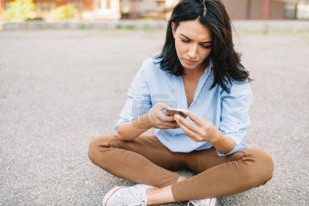 Photo pour Bon à la recherche de femelles dans des vêtements élégants, lit bonne nouvelle sur téléphone mobile, connexion internet Wi-Fi. Messages d'adolescente dans les réseaux sociaux à l'extérieur. Notion de peuple et style de vie. - image libre de droit