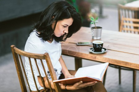 Photo pour Vue latérale d'attrayant caucasien assis à la terrasse du café, de boire du café et de lire le livre au moment de la pause. Concept de mode de vie, les entreprises et les personnes. - image libre de droit