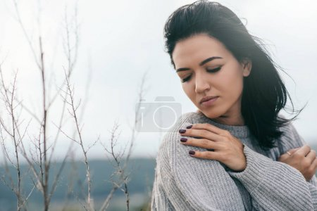 Photo for Young dreamy female with closed eyes with hand on the shoulder, wearing grey sweater. Attractive brunette caucasian young woman with windy hair outdoor. Lifestyle fashion concept. Cover idea. - Royalty Free Image