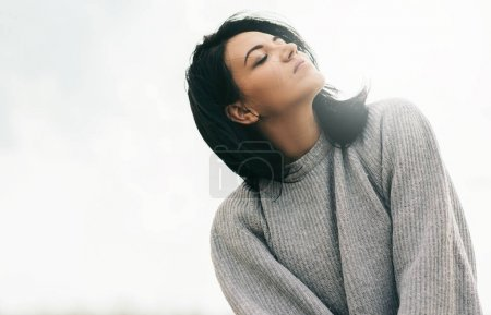 Photo for Attractive brunette caucasian young woman traveler with windy hair, dreaming against sunlight sky. Dreamy female with closed eyes in gray pullover. Lifestyle and people concept. Cover mood. - Royalty Free Image