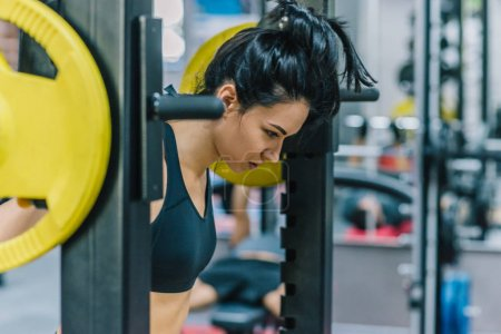 Muscular attractive young woman doing workout in the gym, lifting weights with barbell on shoulders. Hard workout for cross fit. People, sport, fitness, healthy lifestyle and motivation concept.