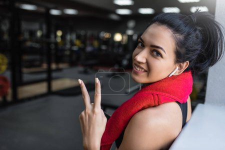 Photo for Beautiful shot of happy young beautful fitness woman taking a break from her workout with red towel on neck and earphones listening the music and showing peace sign in the gym. - Royalty Free Image