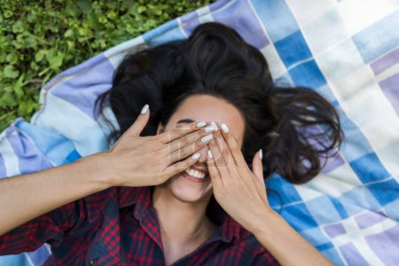 Photo for People and lifestyle concept. Top view of young attractive brunette female wearing plaid shirt hide eyes with hands and smiling. Happy woman with funny face smiling, laughing, showing her white teeth - Royalty Free Image