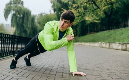 Outdoors horizontal image of young athlete man doing push-ups. Fitness male doing workout exercises in the morning at the park. People and sport concept