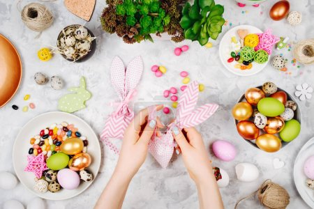 Woman wraps treats in fabric bunny gift bags. Easter concept.