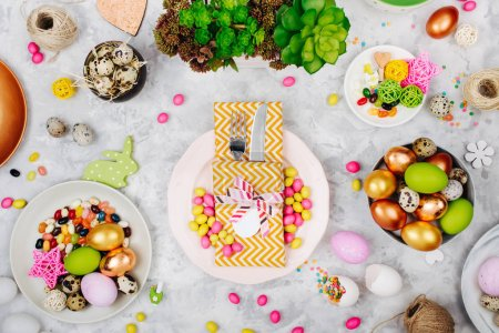 Easter table setting. Painted eggs in trays, candy, flowers, cutlery and napkin