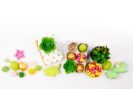 Workspace with easter decoration. Painted eggs in trays, candy, flowers, succulent with copy space. Spring background. Flat lay, top view