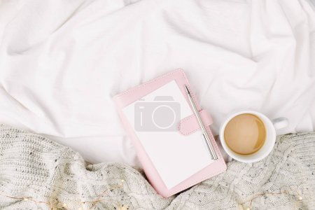 notebook and cup on bed