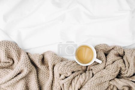 Foto de Taza de café caliente, envuelto en la bufanda, a sábanas - Imagen libre de derechos