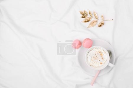 Photo pour Vue du dessus de tasse de café et macarons placés sur les draps - image libre de droit