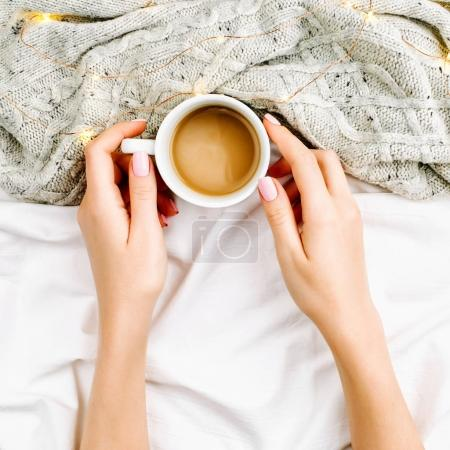 woman holding cup over bed
