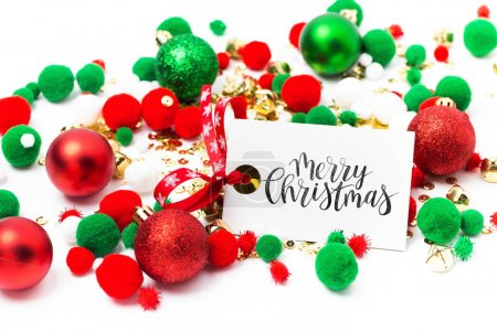 Merry Chrisrmas card and pile of red and green Christmas balls on white background