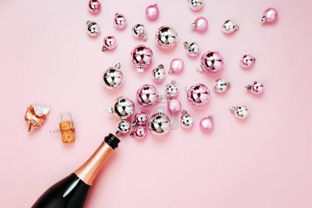 champagne bottle and shiny Christmas balls on pink background, top view