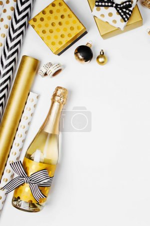 flat lay of champagne bottle, presents and golden wrapping paper rolls on white background