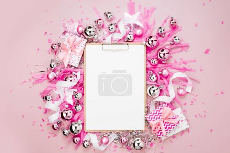 Flat Lay Holiday Background with blank clipboard, Christmas balls, ribbons and gifts in pink colour