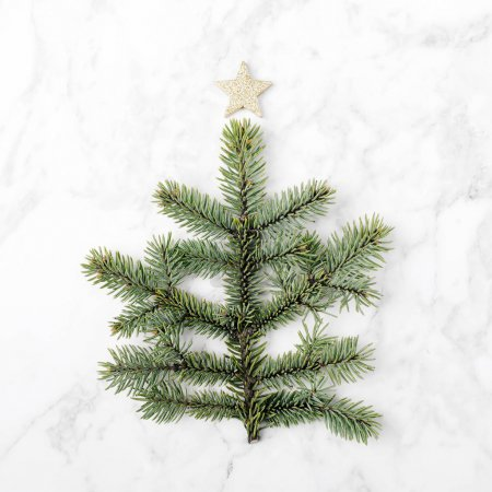 Christmas tree made of green fir branches decorated with star on top
