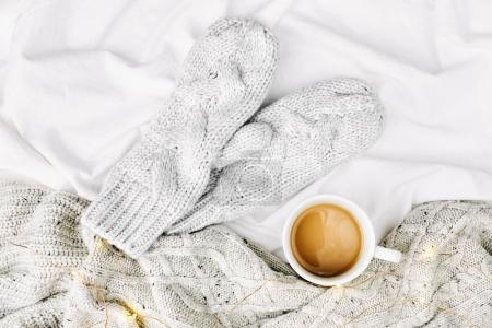 Cup of coffee on bed with warm plaid and mittens