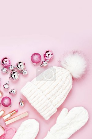 Flat Lay Holiday Background with knitted cap and mittens, Christmas balls in pastel pink colour