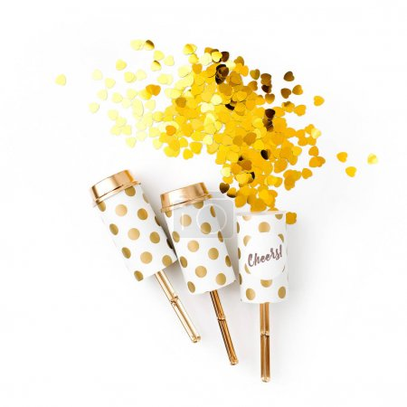festive golden confetti and crackers on white background