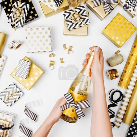 female hands opening champagne bottle on the table with flat lay of golden presents and wrapping paper rolls