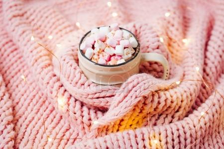cup of cocoa with marshmallows wrapped in pink knitted scarf
