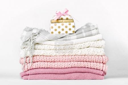 Gift box on stack of warm clothes on white background