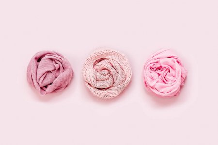 three rolled scarfs of pastel colors on pink background