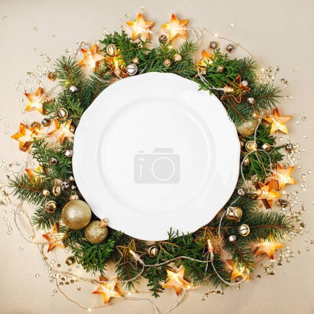 white plate decorated with Christmas wreath of fir twigs, stars, balls and electric garland