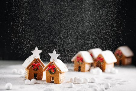 Photo for Homemade Christmas gingerbreads of house shape on marble table - Royalty Free Image