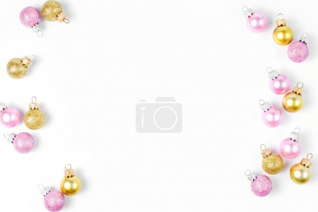 Frame made of pink and golden Christmas balls on white background