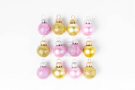 Pink and golden Christmas balls on white background