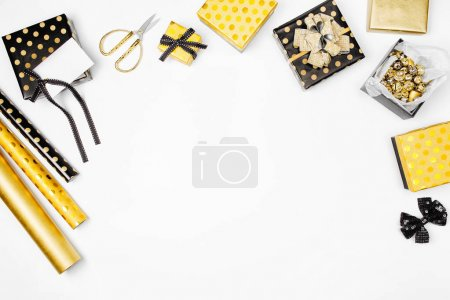 flat lay of golden presents and wrapping paper on white background