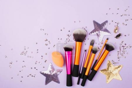 pile of different accessories for makeup on lilac background