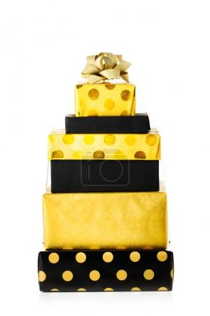 pile of Christmas presents wrapped in yellow and black paper, isolated over white background