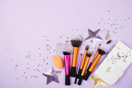 Vue de dessus des tas de différents accessoires de maquillage et pochette sur fond lila
