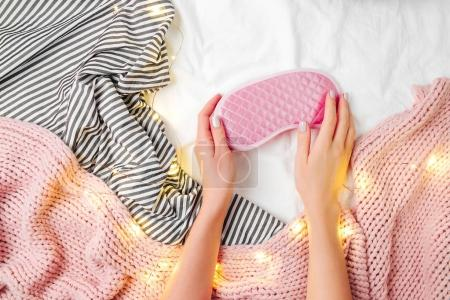 Top view of pink sleep mask and bedding sheets